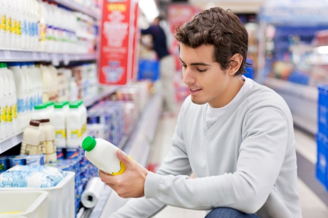 A young man reads the label on a milk bottle in the dairy section of a grocery store.  Horizontal shot.