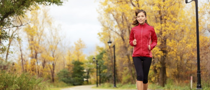 Fall running - woman jogging in autumn in city park.  Female jogger training outside. Beautiful young multi-ethnic woman model in her twenties.